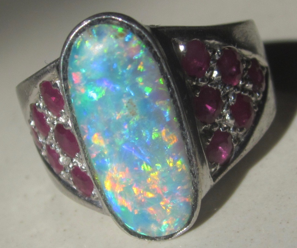 opal ring with 12 rubys on the ring band.
