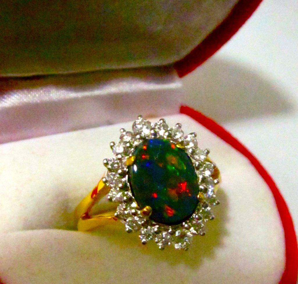 opal ring with diamonds surrounding opal in 18 ^ gold